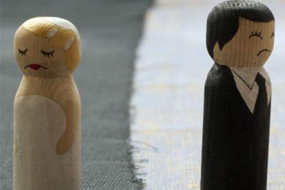 Rozwód dwojga małżonków przedstawiony w formie drewnianych pionków w ślubnym stroju